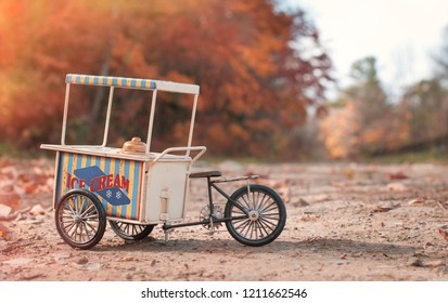 Vintage ice cream cart on wheels  in autumn park in sunny day
