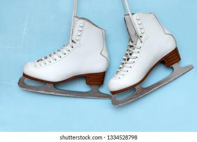 Vintage ice skates for figure skating hanging on the backg