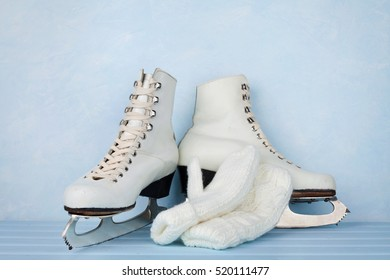 Vintage ice skates for figure skating and knitted mittens on turquoise background
