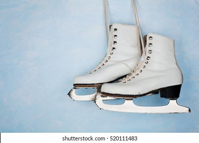 Vintage ice skates for figure skating hanging on the background of blue rustic wall.