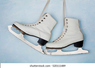 Vintage ice skates for figure skating hanging on the background of blue wall.