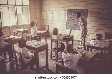 A vintage image of a classroom in an Asian school, a wooden chalkboard classroom, a table and a chair made of wood. Teachers and students wear uniforms.
