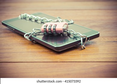 vintage image of pink padlock and chain on mobile,smart phone,tablet,cell phone ,still life,safety privacy data and business data in mobile concept