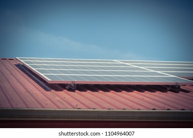Vintage image solar panel on metal roof of commercial building at Gainesville, TX, USA. Photovoltaic solar collector on classic rib steel tile floor. Renewable clean green energy, sustainable economy