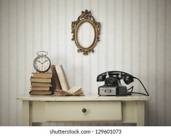 Vintage interior close up with table, books and old phone
