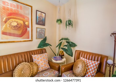 Vintage interior decoration with a retro sofa, magazines,old movies posters,  macrame plant hangers, retro print cushions.