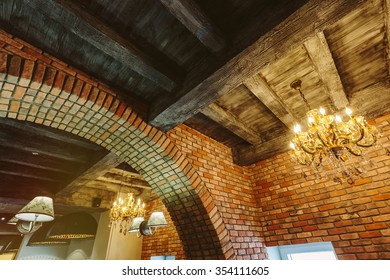 vintage interior design with brick wall, wooden ceiling and retro chandelier