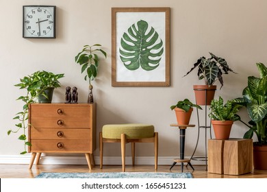 Vintage interior design of living room with stylish retro furnitures, a lot of plants, commode, black clock and brown poster mock up frame on the beige wall. Stylish home decor. Template.  - Shutterstock ID 1656451231