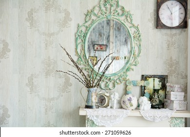 Vintage interior with mirror and a table with a vase and willows. Designer wall clock. Angels on the table
