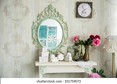 Vintage interior with mirror and a table with a vase and flovers. Designer wall clock. Angels on the table