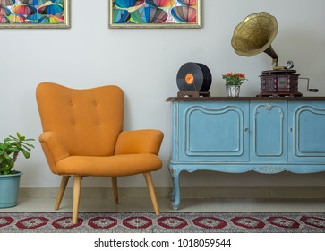 Vintage interior of retro orange armchair, vintage wooden light blue sideboard, old phonograph (gramophone), vinyl records on background of beige wall, tiled porcelain floor, and red carpet