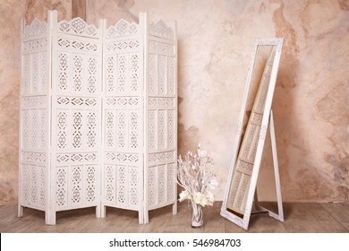 Vintage interior with white delicate decorative wood panel and mirror on brown plaster wall. Boudoir wedding room. Retro folding screen and mirror. Vintage ornate carved folding screen.
