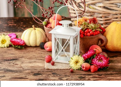 Vintage iron lantern among autumn fruits, vegetables and plants.