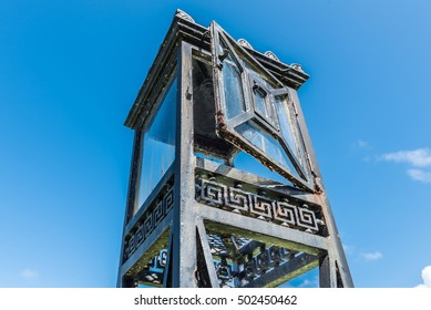 Vintage iron lantern tower with glass doors and stand isolated on blue sky