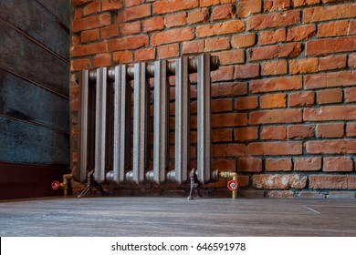 Vintage iron radiator for home with legs. Old cast iron central heating battery.