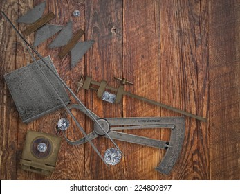 vintage jeweler tools and diamonds over wooden bench, space for text
