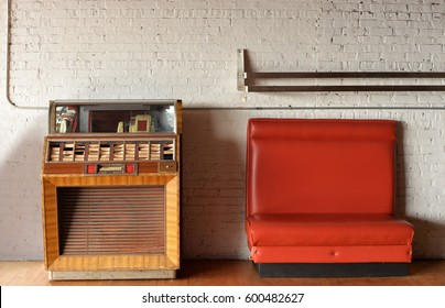vintage jukebox and bench against brick wall