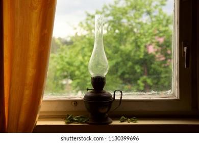 Vintage kerosene lamp on the windowsill, rustic still life, retro object
