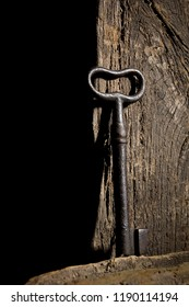 Vintage key hanging on an old log