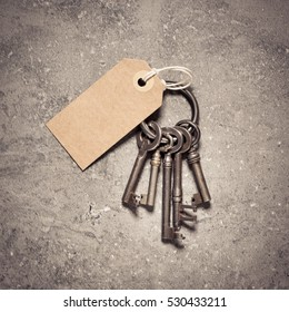 Vintage key set with blank paper tag on stone table. Symbol of new home, security and access.