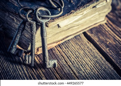 Vintage keys and books on old wooden table