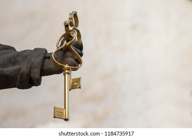 Vintage keys in hand on background. Saint Peter holds the keys in his hand. Concept of the keys of heaven. Blue sky background.