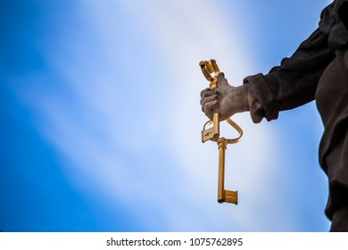 Vintage keys in hand on sky background. Saint Peter holds the keys in his hand. Concept of the keys of heaven. Blue sky background.