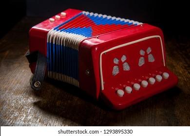 Vintage kids toy musical instrument accordian with dark moody lighting