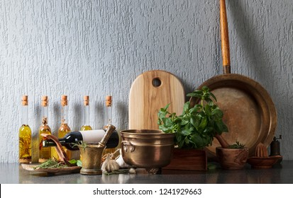 Vintage kitchen utensils with Basil and bottles of olive oil. Olive oil with different spices and herbs. Healthy organic food.