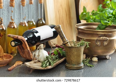 Vintage kitchen utensils with Basil , bottles of olive oil and red wine.
