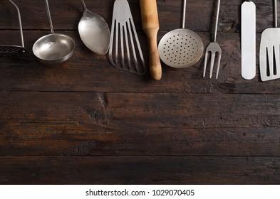 Vintage kitchen utensils on rustic wood background