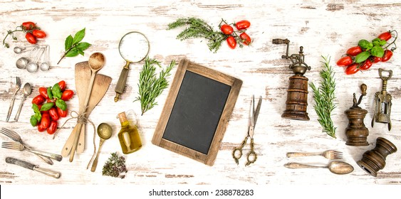 Vintage kitchen utensils with vegetables, herbs and spices. Blackboard for your text