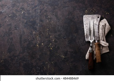 Vintage kitchenware kitchen utensils Meat Fork and Butcher Cleaver on dark background