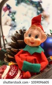 Vintage Knee Hugger Elf in Christmas Basket with Pine cones.