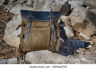 Vintage kraft cloth backpack with leather top stands on stones. HDR image