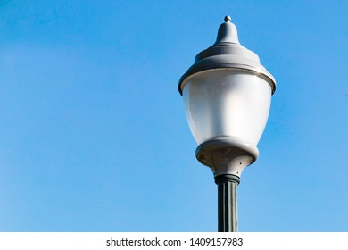 A vintage lamp against the backdrop of a clear blue sky.
