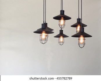 Vintage lamp hanging from the ceiling with white wall.