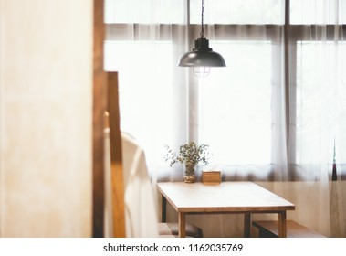Vintage lamp hanging from the ceiling with wooden table in the room