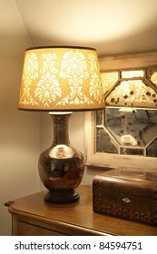 A vintage lamp on a table with decorations in the corner