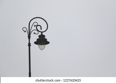 Vintage lamp post, single city light on grey sky,  mist street light background, autumn lamp post travel, depression, loneliness,
