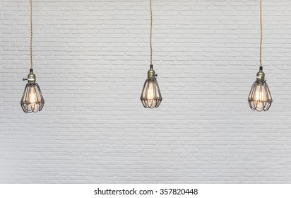 vintage lamps hanging from the ceiling with white brick wall
