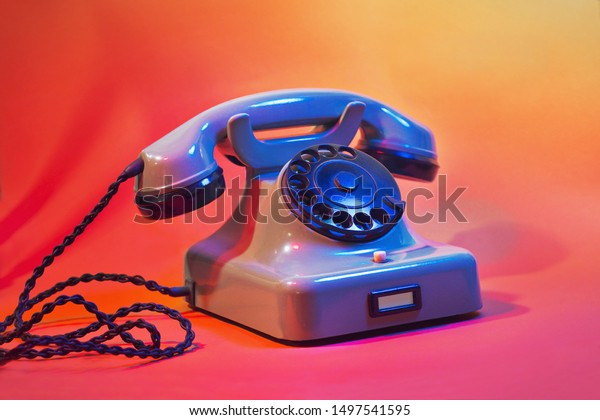 A vintage, landline cable telephone in colorful background. A symbol of traditional telephony, communications or contact