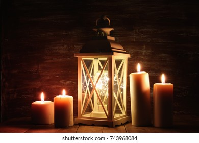 Vintage Lantern with burning candles on wooden table