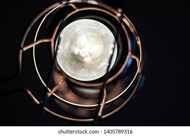 A vintage lantern with an illuminated light bulb.