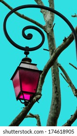 Vintage lantern magenta color glass and the tree twigs. (Arles, Provence, France) Toned image.