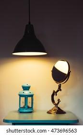 Vintage lantern with mirror on table