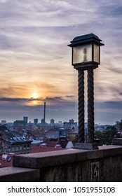 A vintage lantern on Upper Town Zagreb, overlooking the cityscape below during the sunset.