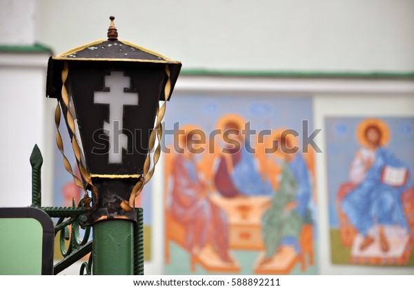 Vintage lantern with an Orthodox cross closeup on the blurry background of religious murals. Slonim, Belarus.