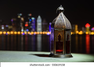Vintage lantern. Ramadan mood at night with light of Doha city in the background.