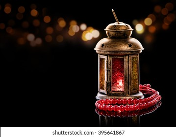Vintage lantern with red rosary. Ramadan mood at night with light decoration in the background.